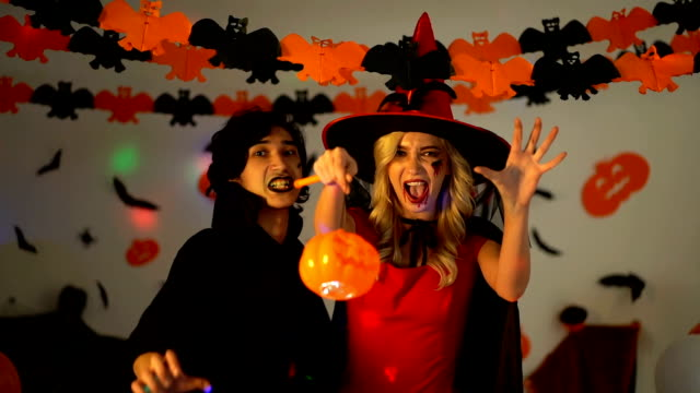 Trick Or Treat! Young Man Wearing Vampire Costume And Beautiful Woman Wearing Witch Costume Trying To Be Scary At Halloween Party