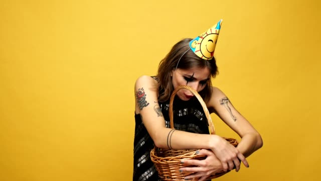 Tricky lady with halloween make up and holiday cap teasing with candies and laughing isolated over yellow video