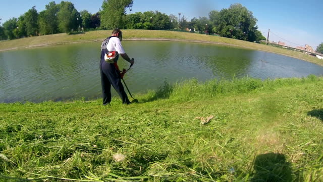 Trimming Grass A worker mowing the grass with a lawn trimmer. riverbank stock videos & royalty-free footage