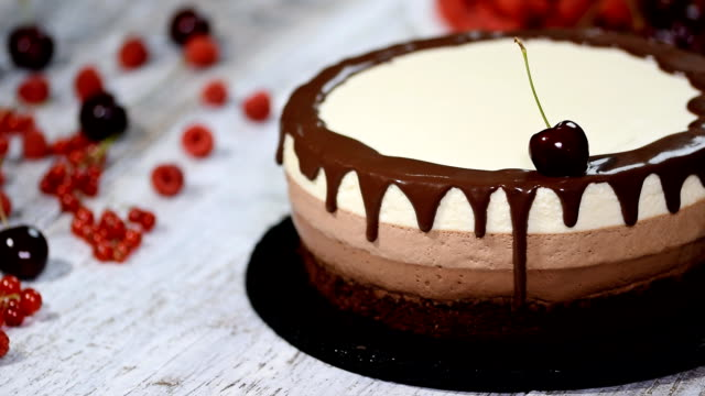 triple chocolate mousse cake decorated with fresh berries. - decorazione per dolci video stock e b–roll