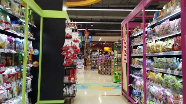 Trolley moving through aisle in supermarket Chiang Rai, Thailand: June 15, 2020 - Trolley slowly moving through aisle in supermarket. snack aisle stock videos & royalty-free footage