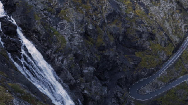 hd trollstigen road norway slow motion cars and waterfall aerial - аксессуар для волос стоковые видео и кадры b-roll
