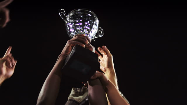 A trophy being held in the air by a sports team video