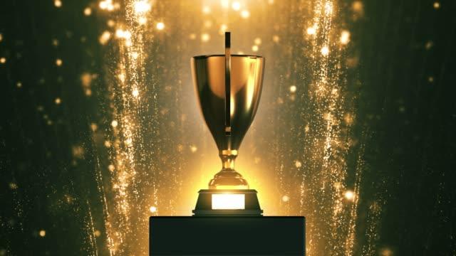 vídeos de stock, filmes e b-roll de troféu 3d com partículas de ouro fundo 4k looped - troféu