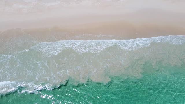 тропический вид с воздуха на пляж, вид на волны на тропическом белом песчаном пляже. морские волны бесшовные петли на красивом песчаном пля� - спокойная вода стоковые видео и кадры b-roll
