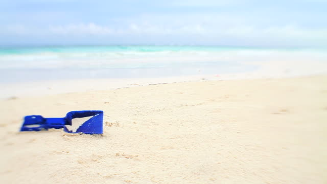 Tropical beach holiday blue spade forgotten in sand video