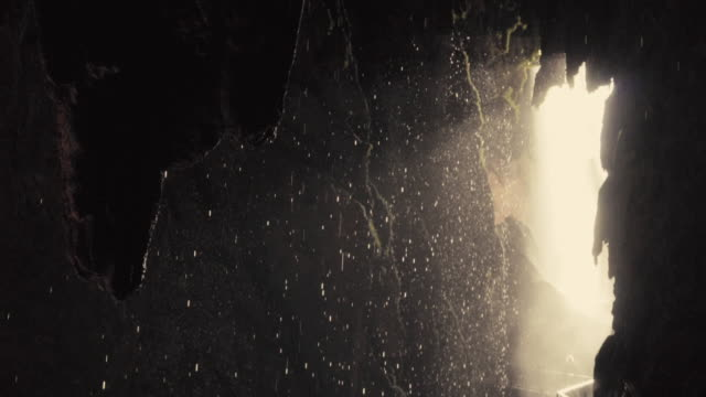 Tropical cave interior, water drops falling in slow motion.