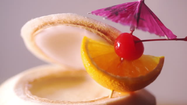 Tropical fresh coconut cocktail decorated with umbrella, slices of orange and maraschino cherry.