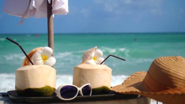 新鮮なココナッツのトロピカル カクテルは、プルメリアのお花、帽子、傘、ターコイズ ブルーの海の背景に変更フォーカスを持つビーチ カフェでサングラスに装飾されています。スルヲ概念。1920 x 1080 - サムイ島点の映像素材/bロール
