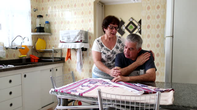 Troubled senior couple at home kitchen. Older married couple going through struggle