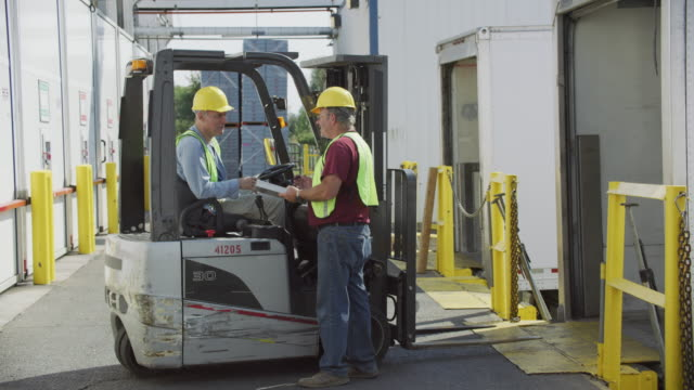 Truck driver and forklift driver talk at shipping facility. Truck driver and forklift driver talk at shipping facility.  Fully released for commercial use. forklift stock videos & royalty-free footage
