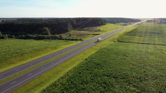 Truck Driver Carrying Cargo On Speed Highway At Sunset Background Aerial View