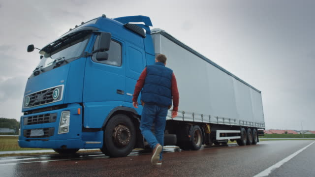 truck driver crosses the road in the rural area and gets into his blue long haul semi-truck with cargo trailer attached. logistics company moving goods across countrie and continent - тягач с полуприцепом стоковые видео и кадры b-roll