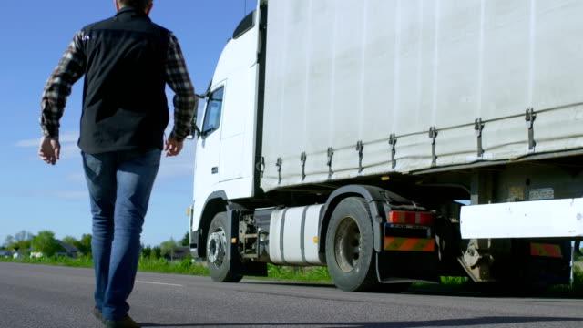 Conductor del camión cruza la carretera en la zona Rural y se pone en su blanco camiones con remolque de carga. Sol brilla y la carretera está vacía. - vídeo