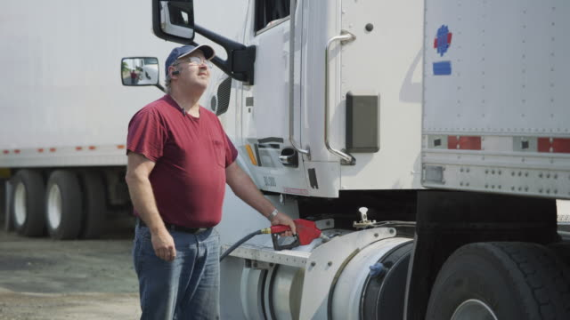 Truck driver filling up fuel tank of semi truck. Truck driver filling up fuel tank of semi truck.  Fully released for commercial use. refueling stock videos & royalty-free footage