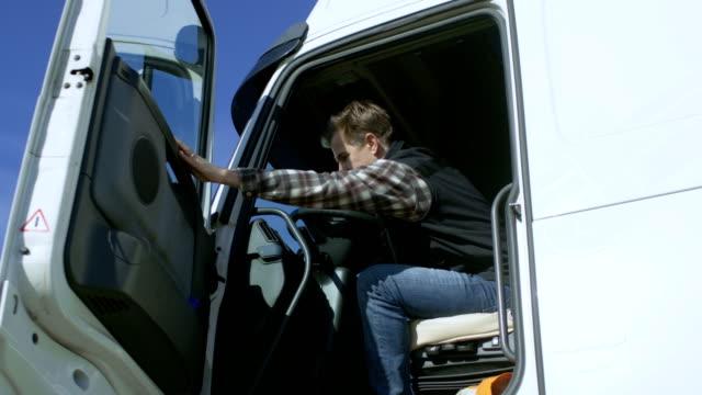 Truck Driver sale de blanco aparcado su Cab-Over Truck. El día es soleado, conductor profesional. - vídeo