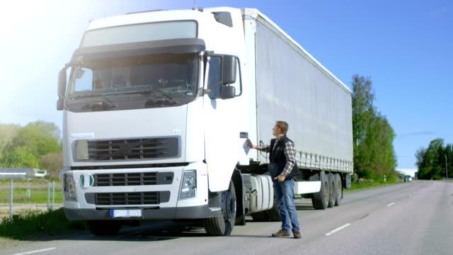 Conductor de camión con carga de documentos carpeta sale de blanco aparcado su Cab-Over Truck y cruza la carretera. - vídeo