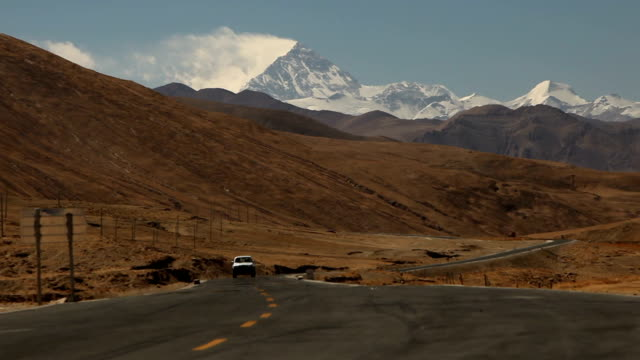 Truck Driving Down Road in Tibetan Mountains video