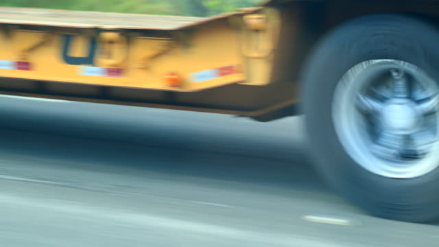 Truck driving on highway road. Closeup of truck tires speeding on asphalt road in 4K video