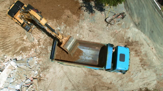 AERIAL Truck going backwards towards the excavator loading it with soil