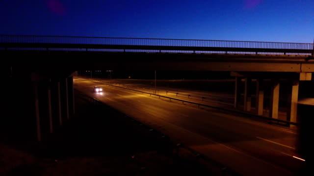 Carro se mueve a lo largo de la carretera bajo el puente. Vista aérea. Tráfico en cruce de la carretera iluminada. Tráfico de la tarde. - vídeo
