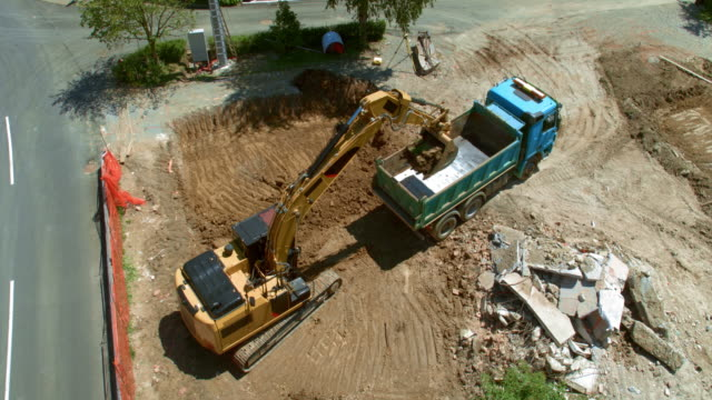 AERIAL Truck moving backwards so the excavator can load it with soil at the sunny building site