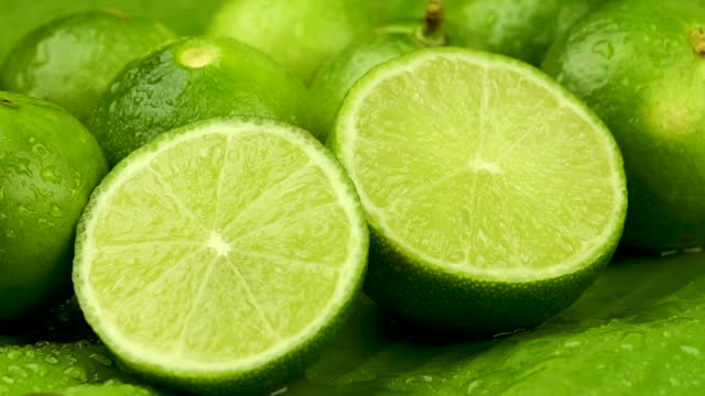 Truck shot of half and whole fresh lime juicy on green banana leaves