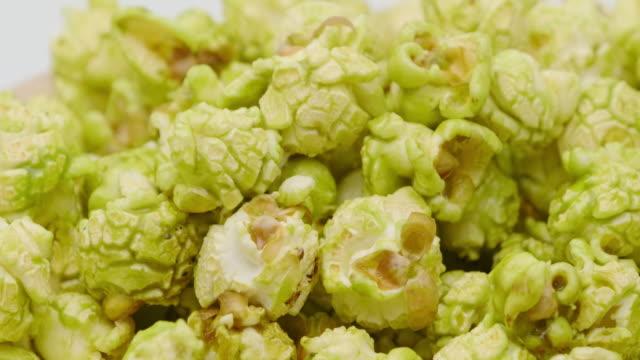 truck shot of japanese matcha green tea popcorn in the wooden bowl bulk isolated on white background - gotowy do jedzenia filmów i materiałów b-roll