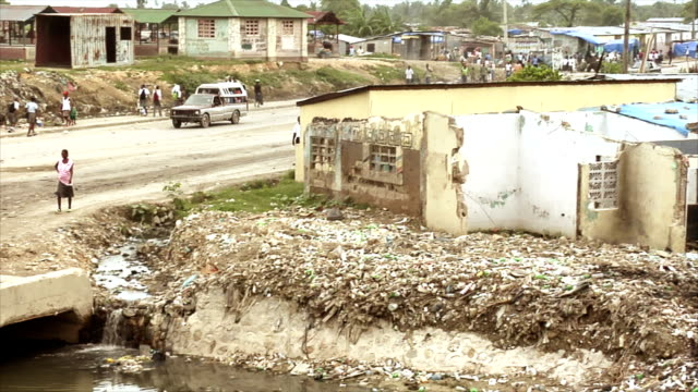 Truck Taxi Driving Across Trash Filled Stream A panning shot following a truck taxi as it crosses a bridge over a garbage filled stream, shot in Haiti earthquake stock videos & royalty-free footage
