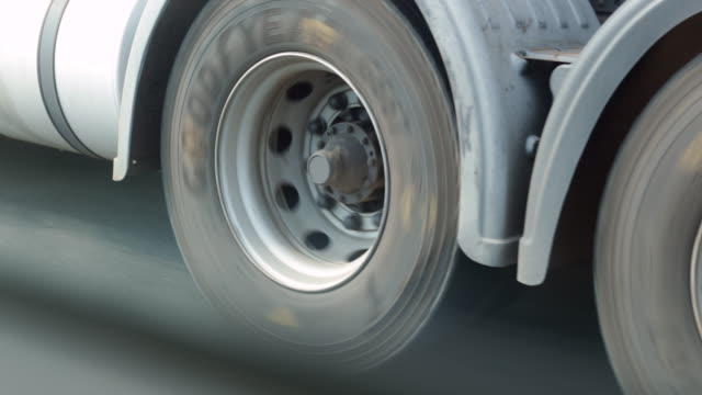 Truck tires rotating on highway road in 60fps slow-motion in 4K video
