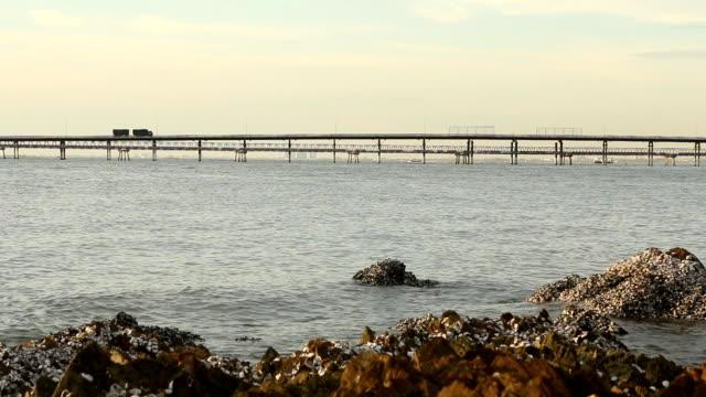 Truck with trailer on bridge over sea. video