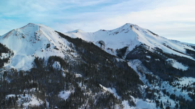 Trucking Back Aerial Drone Shot of Snowy Mountain Peaks of the San Juan Mountain (Rocky Mountain Range Near Red Mountain Pass) Outside of Ouray, Colorado in Winter Surrounded by a Forest of Trees Trucking Back Aerial Drone Shot of Snowy Mountain Peaks of the San Juan Mountain (Rocky Mountain Range Near Red Mountain Pass) Outside of Ouray, Colorado in Winter Surrounded by a Forest of Trees snowcapped mountain stock videos & royalty-free footage