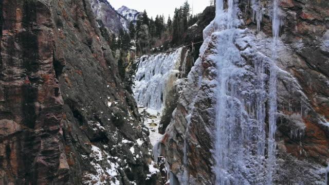 vídeos y material grabado en eventos de stock de camiones drone posterior disparo de un cañón de montaña estrecha con nieve, una corriente, una pared de hielo (ice park) y una cascada congelada en ouray, colorado - estrecho