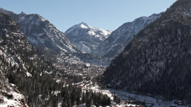 trucking forward aerial drone shot of snowy forests of trees and snowcapped peaks of the san juan mountains (rocky mountains) above ouray, colorado under a clear sky - скалистые горы стоковые видео и кадры b-roll