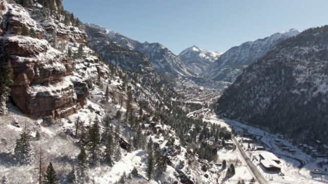 trucking forward aerial drone shot of snowy forests of trees and snowcapped peaks of the san juan mountains (rocky mountains) above the town of ouray, colorado under a clear sky - колорадо стоковые видео и кадры b-roll