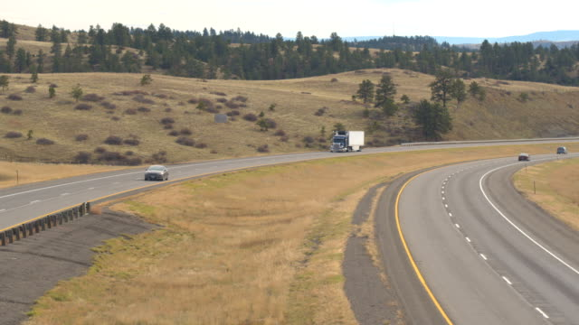 AERIAL: Trucks and cars driving on highway approaching the Rocky Mountains video