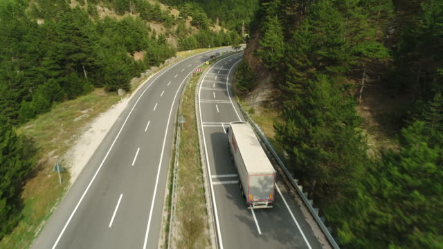 Trucks driving, traveling on the forest asphalt road aerial footage. Highway truck traffic