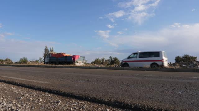 vídeos de stock e filmes b-roll de trucks going on the road with rubbish on roadside - berma da estrada