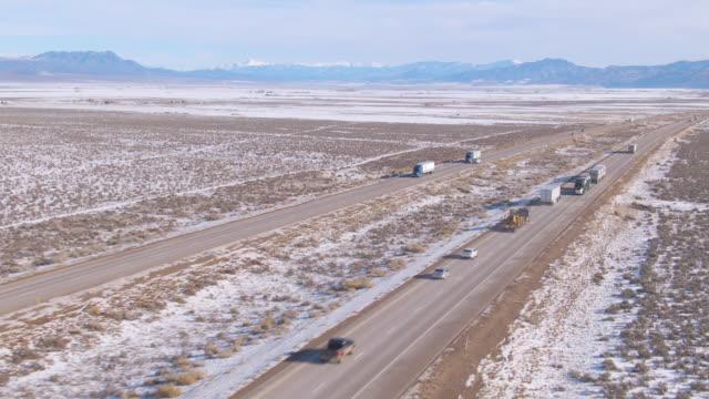 drone: lastwagen schleppen fracht auf einer autobahn, die über die verschneite landschaft in utah führt. - utah stock-videos und b-roll-filmmaterial