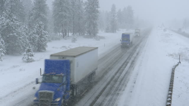 Trucks haul containers across the state of Washington and through a snowstorm. video