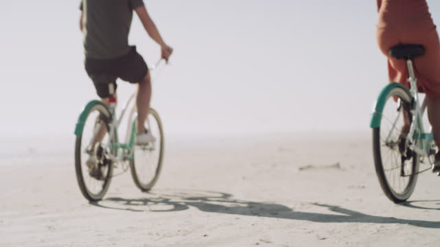 True love moves mountains, and bicycle wheels 4k video footage of a happy young couple going for a bicycle ride at the beach coastal feature stock videos & royalty-free footage
