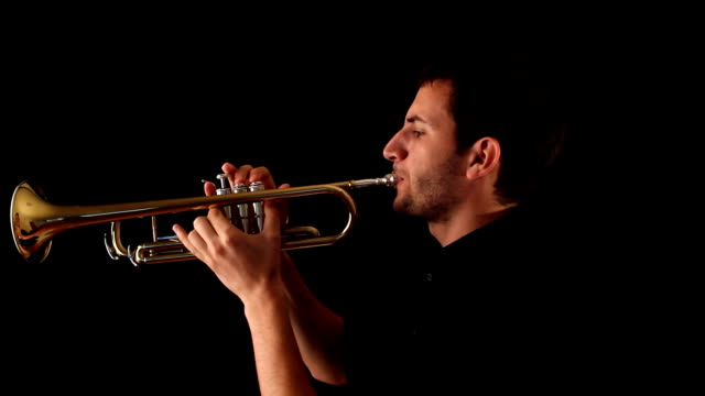 Trumpet player against a black background video