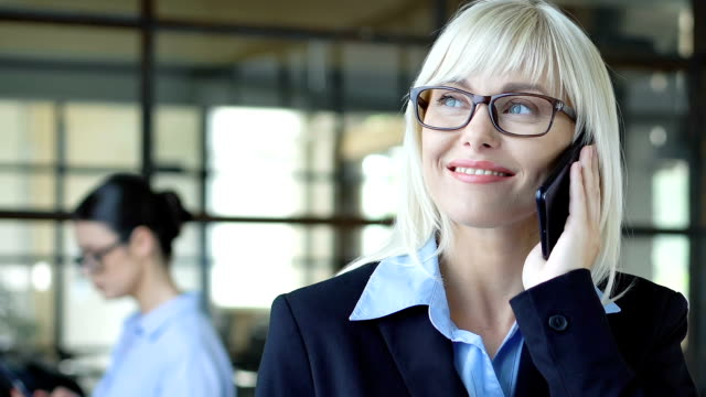Trustworthy woman in suit listening to client on phone, business consulting 24-7