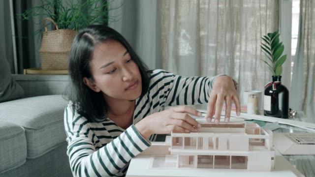 vídeos de stock e filmes b-roll de trying to design modern flat roof with mass model - arquiteto