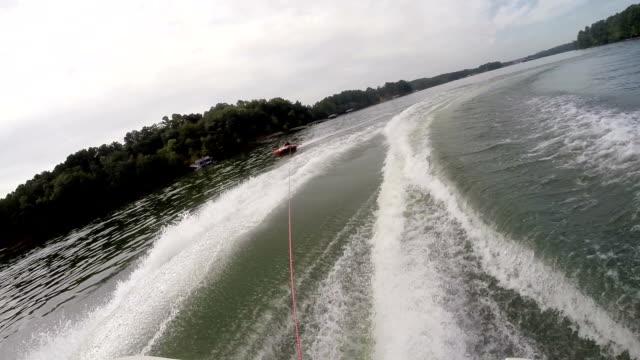stockvideo's en b-roll-footage met tubing on a lake behind a ski boat - opblaasband