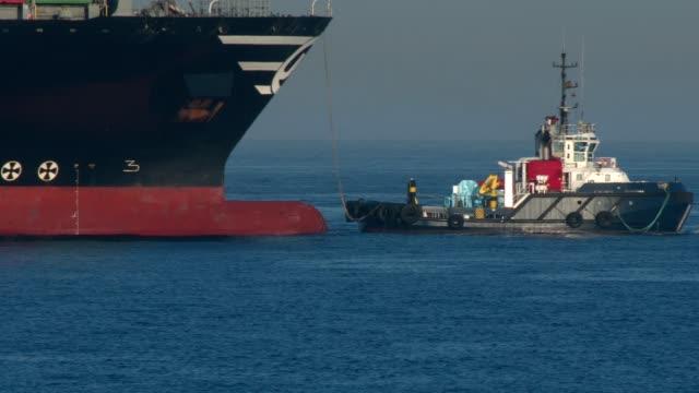 tug boat assists container ship - rimorchiatore video stock e b–roll