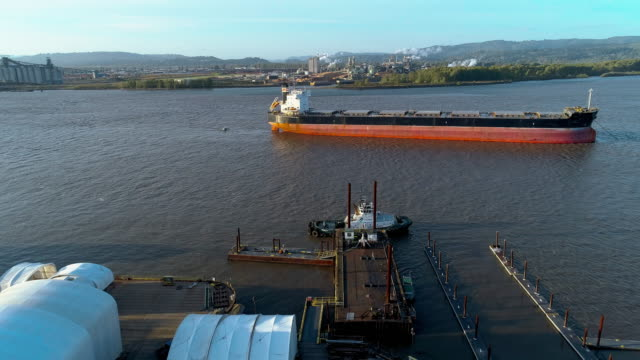 Tugboat on the small commercial pier, and the cargo ship on anchorage at Columbia River, on the border between states Oregon and Washington, USA. Drone aerial low altitude video with the forward camera motion.