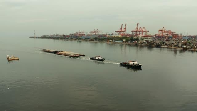 tugboat pulling heavy loaded barge - rimorchiatore video stock e b–roll
