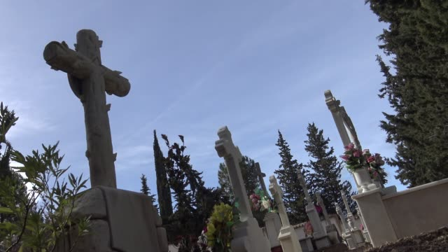 4K Tumbs In A Cemetery with headstone, white cross and cypress in Spain.