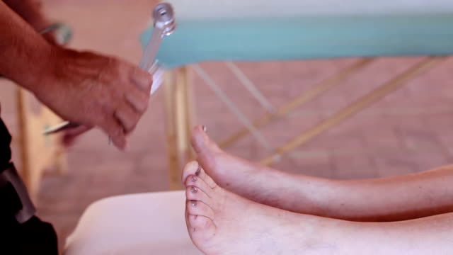 tuning fork massage on feet: relaxing, alternative medicine, chiropractor - icona posate video stock e b–roll